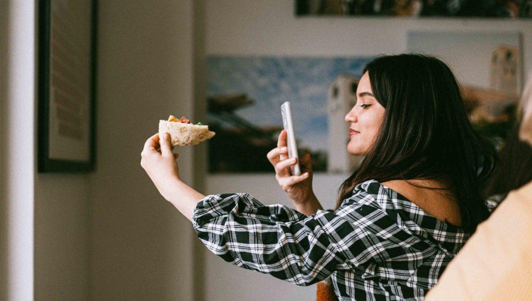 Cómo vender en Instagram. Joven sosteniendo Pizza